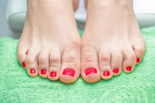 Pieds féminins avec vernis à ongles rouge