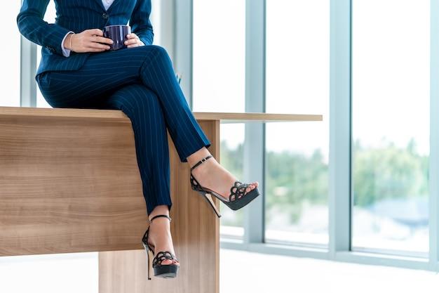 Pieds de femme d'affaires tout en étant assis sur une tablette