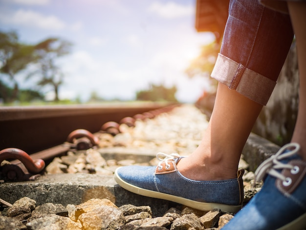 Pieds de femme en baskets bleus assis près de la voie ferrée. concept de vacances et de voyage.