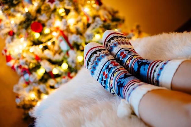 Pieds de femme en chaussettes de laine à l'arbre de noël.