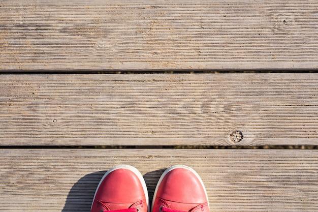 Pieds de femme en chaussures de sport sur le fond de la jetée en bois.