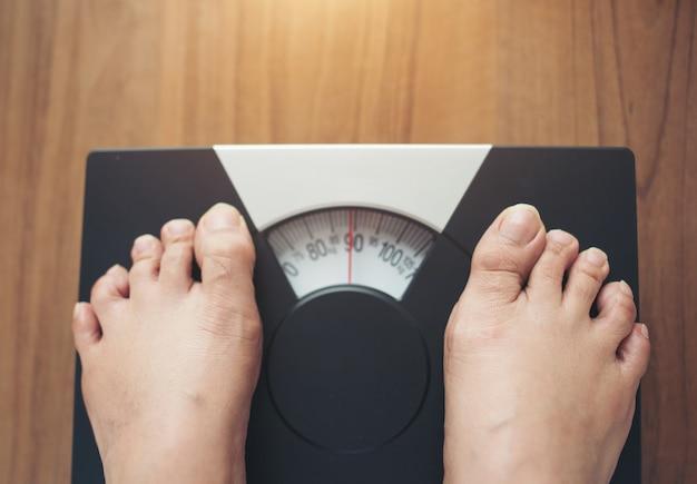 Pieds de femme debout sur une échelle de poids sur fond en bois