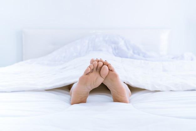 Pieds d'une femme dormant dans un lit à la maison. - jambes d'une femme allongée sur un lit blanc.