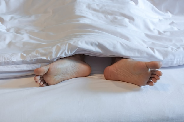 Pieds de femme endormie dans la chambre à coucher blanche