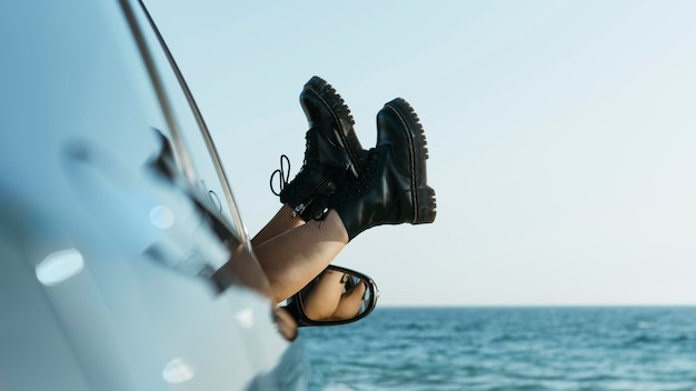 Pieds de femme hors de la fenêtre de la voiture près de la mer