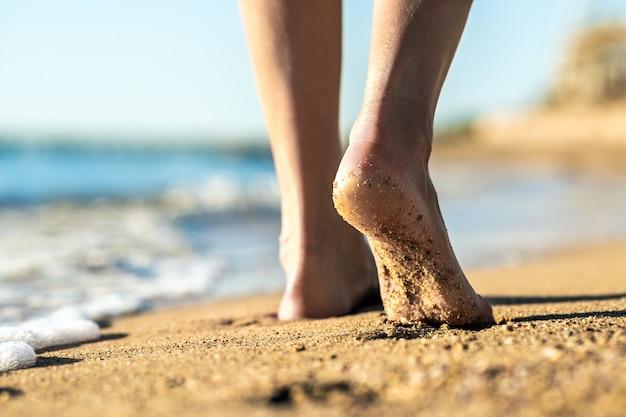 Pieds de femme marchant pieds nus sur le sable laissant des empreintes