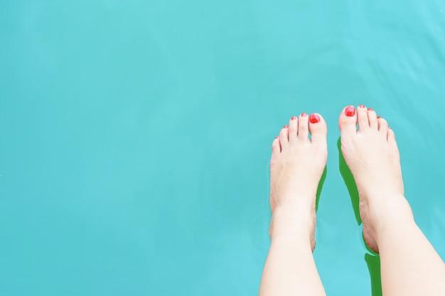 Pieds de femme avec des ongles rouges sur l'eau bleue