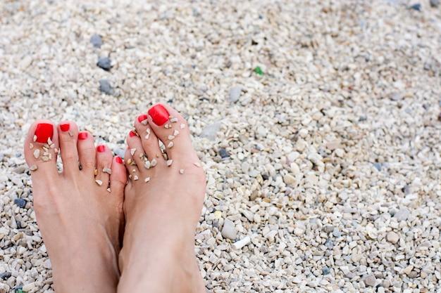 Les pieds de la femme avec des ongles rouges à la plage
