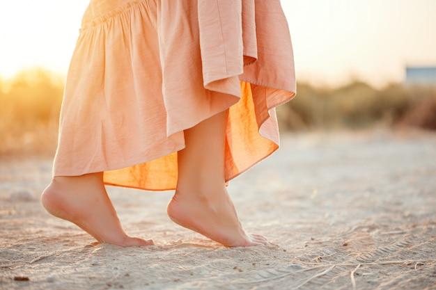 Pieds d'une femme en robe rose marchant sur le sable pendant le coucher du soleil