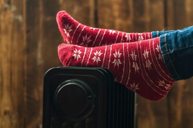 Pieds des femmes à noël, chaussettes chaudes et hivernales sur le radiateur. garder au chaud en hiver, les soirées froides. saison de chauffage