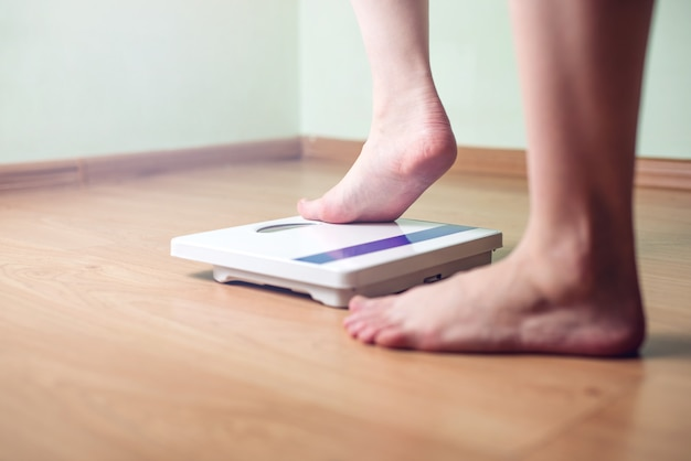 Les pieds des femmes sont sur des échelles mécaniques pour contrôler le poids
