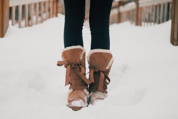 Pieds de fille dans des bottes chaudes en hiver sur le sol enneigé
