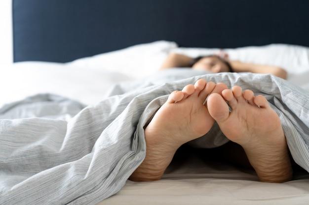 Pieds d'une fille endormie dans son lit le matin.
