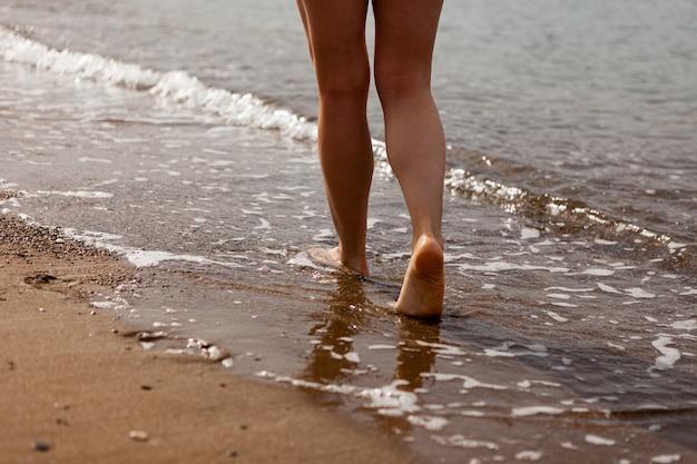 Les pieds d'une fille marchant sur le sable le long de la côte de la mer. sable et eau de mer. la fille marche sur le sable. arrêtez le gros plan.