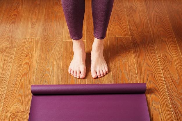 Les pieds de la fille se tiennent devant un tapis de yoga déplié sur le plancher en bois. cours de yoga, exercices d'asanas