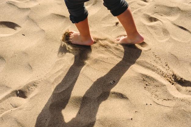 Pieds de garçon marchant sur le sable de la plage.