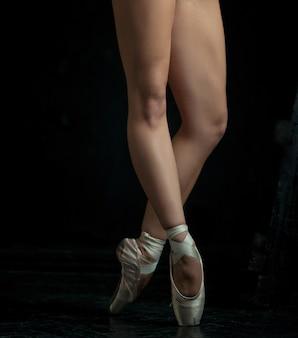 Les pieds en gros plan de la jeune ballerine en chaussons de pointe sur le fond noir