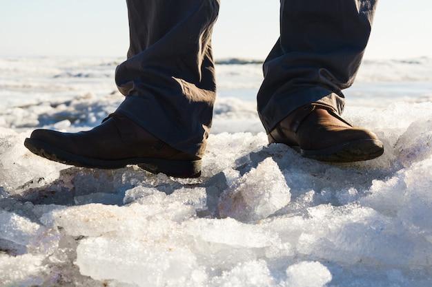 Pieds d'homme en bottes marron et pantalon gris sur mer gelée