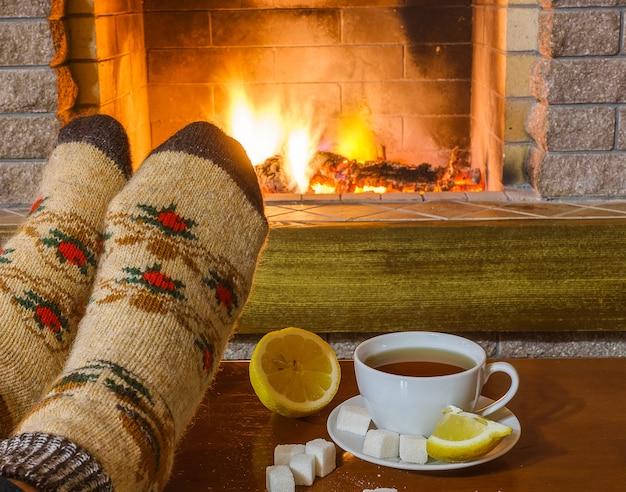 Pieds d'homme en chaussettes; devant la cheminée dans la maison de campagne confortable.