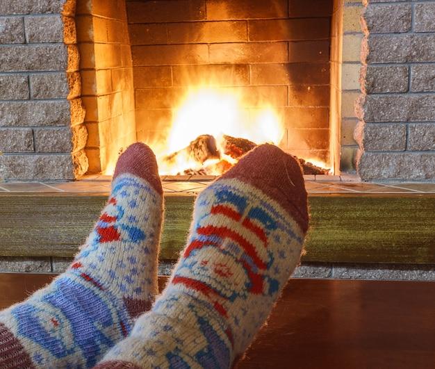 Les pieds de l'homme dans les chaussettes devant la cheminée dans la confortable maison de campagne.