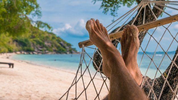 Pieds d'homme dans un hamac, détente sur la plage de haad rin, ko phangan. thaïlande