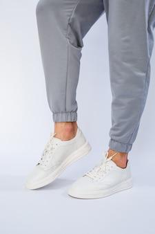 Pieds d'hommes en baskets blanches de tous les jours en cuir naturel sur laçage.