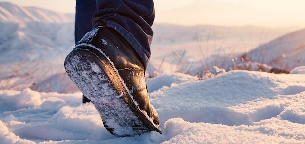 Pieds d'hommes en bottes dans la neige marchant en hiver
