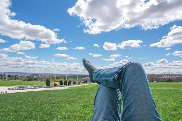 Les pieds des hommes dans les chaussettes sur la détente dans le parc avec skye bleu