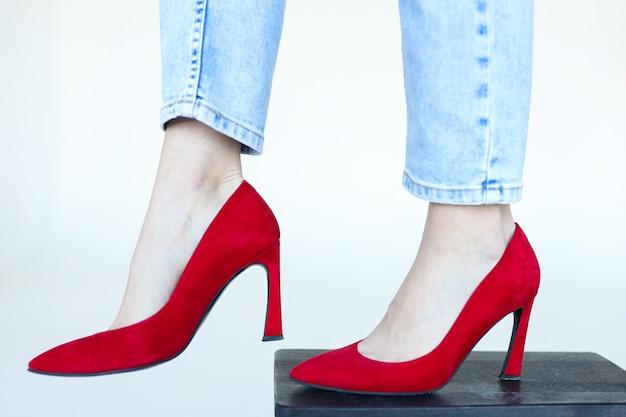 Pieds en jeans et chaussures à talons rouges sur fond blanc