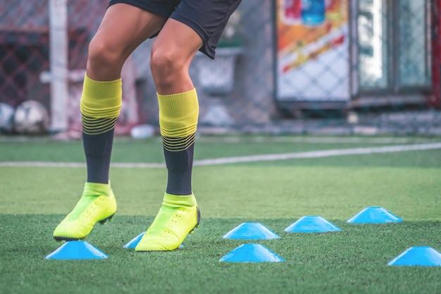 Pieds de joueur de football s'entraîne avec un marqueur dans une académie de football
