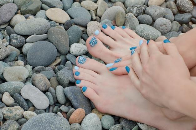 Pieds et mains féminines avec une manucure bleue sur des galets
