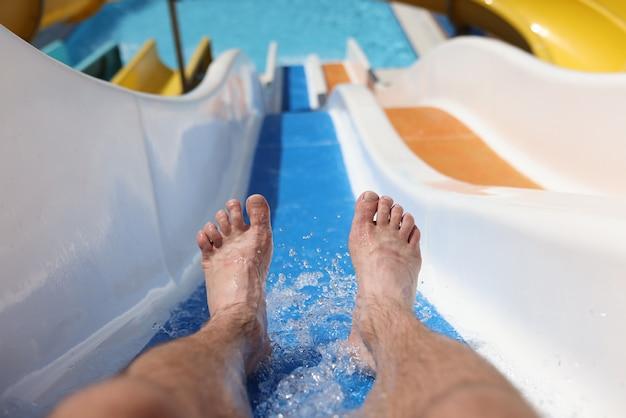 Pieds mâles avec éclaboussures d'eau sur la diapositive dans le parc aquatique