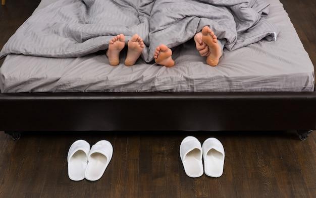 Pieds masculins et féminins, main de l'homme se grattant les pieds sous une couverture grise dans un lit moderne et élégant près de deux paires de pantoufles blanches