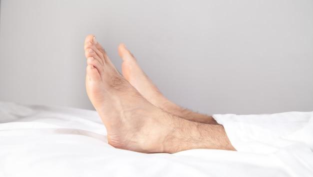 Pieds masculins sur le lit le matin.