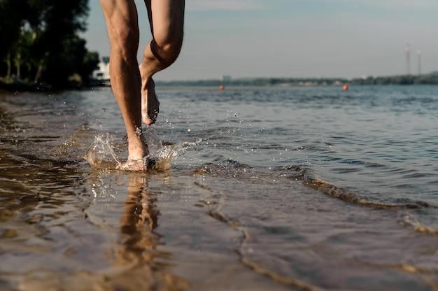Pieds masculins musculaires courant le long de la magnifique rive du fleuve
