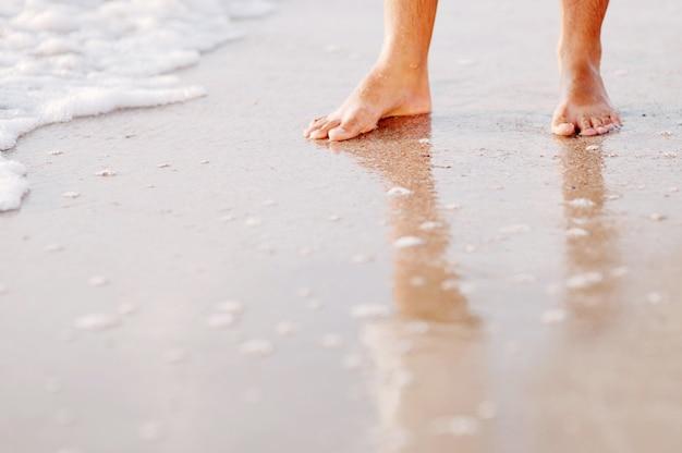 Pieds masculins avec un pantalon retroussé pataugeant sur le rivage