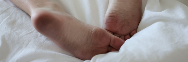 Des pieds masculins sales se trouvent sur un lit blanc et propre