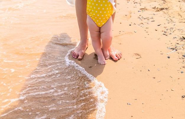 Pieds de la mère et du bébé au bord du rivage