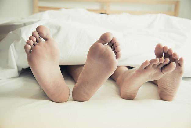 Pieds nus d'amoureux sous couverture dans la chambre
