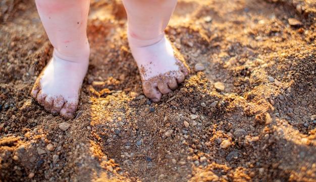 Les pieds nus des enfants en été sur un gros plan de plage de sable doré. le concept de la sécurité des enfants. le concept de loisirs avec les enfants.