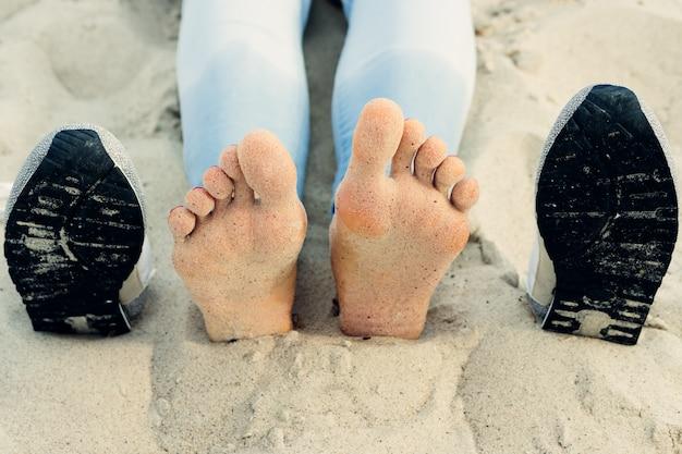 Pieds nus de femmes sur le sable à côté des chaussures