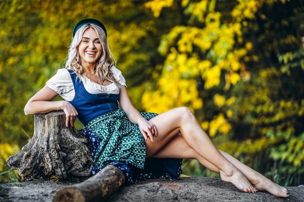 Pieds nus heureuse jolie fille blonde en dirndl, robe traditionnelle du festival de la bière, assis à l'extérieur avec des arbres colorés estompés derrière