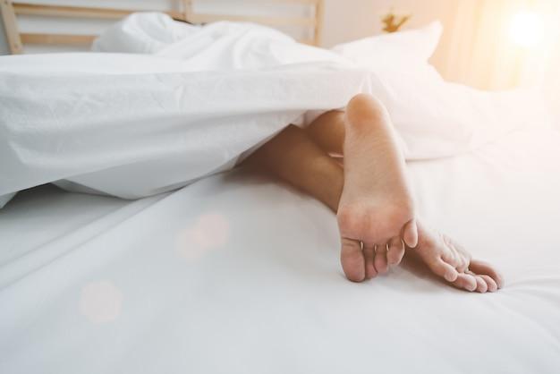 Pieds nus de l'homme sur le lit le matin