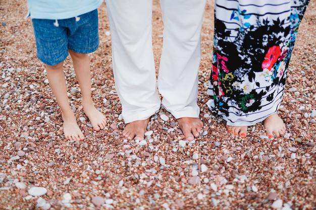 Les pieds nus d'un homme en pantalon léger, une femme en jupe colorée et un enfant en short se tiennent sur un