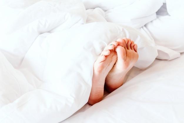 Pieds nus de la jeune femme sur une couverture blanche