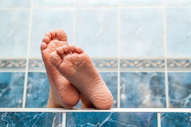 Pieds nus ridés sortant d'une baignoire. jeune personne obtenant un bain pieds gros plan intérieur dans la salle de bain interrior photo