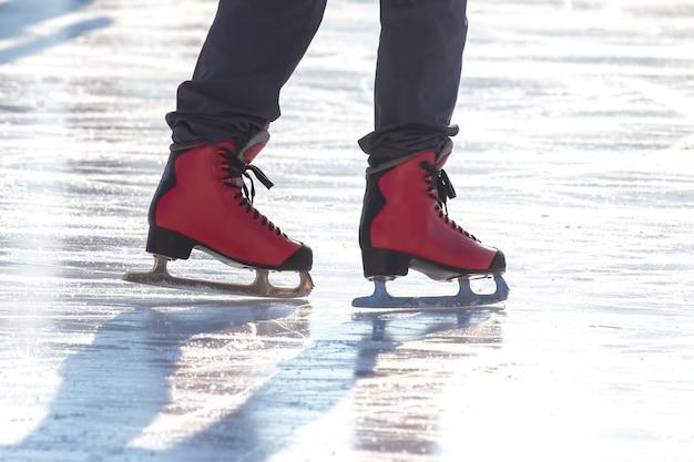 Pieds en patins rouges sur une patinoire. passe-temps et loisirs. sports d'hiver