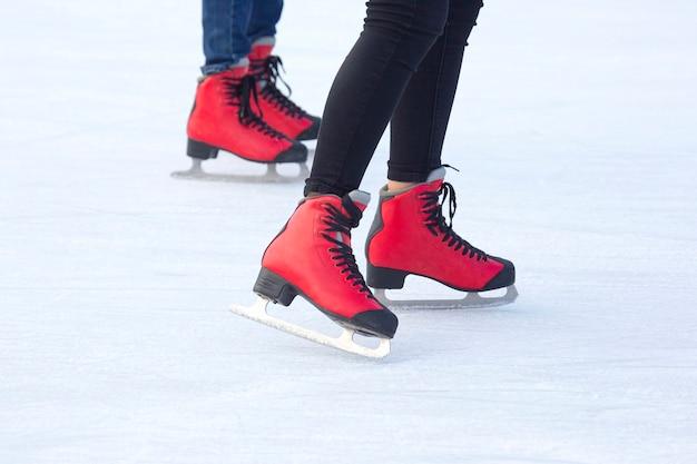 Pieds en patins rouges sur une patinoire. passe-temps et sports. vacances et activités hivernales.