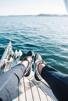 Les pieds de la personne sur le bateau naviguant sur la mer pendant la journée