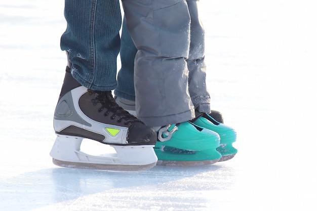 Pieds de personnes différentes patinant sur la patinoire. sports et vacances d'hiver